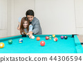Happy couples are playing billiards in home, 44306594