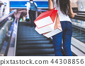 Women are going up the escalator to go shopping. 44308856