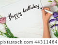 Happy birthday congratulations. Calligrapher writes with black ink on white card. Calligraphy 44311464