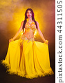 Tempting sexy traditional oriental belly dancer girl dancing on yellow neon smoke background. Woman 44311505