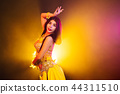 Seductive sexy traditional oriental belly dancer girl dancing on yellow neon smoke background. Woman 44311510