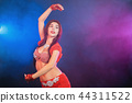 Woman in exotic shining red costume sexually moves her body. Sexy traditional oriental belly dancer 44311522