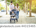 happy family with baby carriage walking in the park 44315465