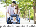 happy family with baby carriage walking in the park 44315466