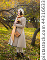 melancholic women in light coat and beret in park 44316633
