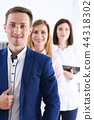 Group of smiling people stand in office looking 44318302