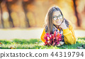 Portrait of a smiling young girl with bouquet. 44319794