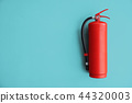 Red Fire extinguisher on the blue wal.l 44320003