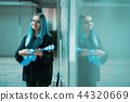 Young pretty girl with blue hair playing on blue ukulele in the underpass or subway. 44320669