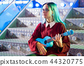 Young pretty girl with blue hair playing on blue ukulele while sitting on glowing neon stairs in 44320775