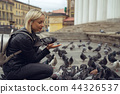 Young beautiful woman is feeding pigeons with bread crumbs in the town square on autumn day 44326537