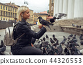 Young beautiful woman is feeding pigeons with bread crumbs in the town square on autumn day 44326553
