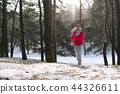 Female runner jogging in cold winter forest wearing warm sporty running clothing and gloves. 44326611