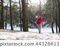 Female runner jogging in cold winter forest wearing warm sporty running clothing and gloves. 44326613