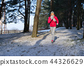 Female runner jogging in cold winter forest wearing warm sporty running clothing and gloves. 44326629