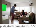 Happy Gay Couple Watching Sports Game On TV At Home 44330772