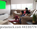 Happy Gay Couple Watching Sports Game On TV At Home 44330774
