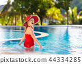 Child with hat in swimming pool. Tropical vacation 44334285
