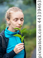 Woman sniffing a branch of a tea 44339463