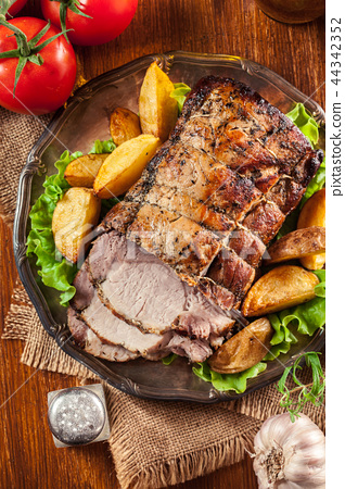 Roasted pork loin with baked potatoes and herbs 44342352