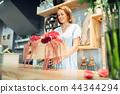Female florist puts flowers in a vase, floral shop 44344294