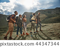 Five young hikers walking in the mountains and smiling 44347344