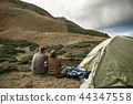 Horizontal photo of two hikers sitting near their tent 44347558