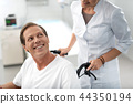 Man in wheelchair looking at lovely nurse with smile 44350194