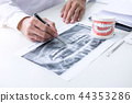 Male doctor or dentist writing report working with tooth x-ray f 44353286