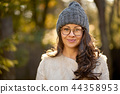 beautiful woman in a cap and glasses on a background of autumn forest 44358953