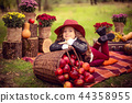 Smiling child with basket of red apples sitting in autumn park 44358955