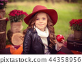 Smiling child with basket of red apples sitting in autumn park 44358956