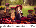 Smiling child with basket of red apples sitting in autumn park 44358957