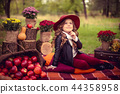 Smiling child with basket of red apples sitting in autumn park 44358958