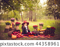 Smiling child with basket of red apples sitting in autumn park 44358961