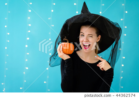 Young woman with a witch hat holding a halloween pumpkin 44362574