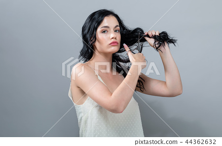 Woman cutting her hair with scissors 44362632