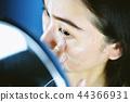 Asian woman applying cosmetics makeup. 44366931