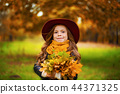 Portrait of a smiling young girl who is holding in her hand a bouquet of autumn maple leaves. 44371325