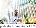 A portrait of businessman with smartphone standing in city, text messaging. 44374179