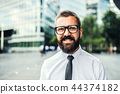 A close-up portrait of hipster businessman with glasses in the city. 44374182
