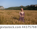a woman farmer in field of wheat before the harvest 44375768