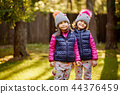 two little girls in a cap and jacket are standing on the grass in an autumn forest 44376459