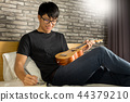 Happy young asian man playing ukulele sitting on bed in bedroom. 44379210