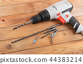 The new drill on wooden background close up 44383214
