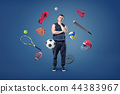 A thoughtful muscular man stands surrounded by different sport gear flying around him. 44383967