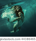 Girl swims under water 44386465
