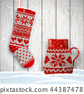 knitted christmas stocking and red tea cup in 44387478