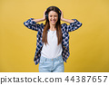 Young woman using phone for listening to music on color background. 44387657