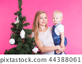 Holidays, family and christmas concept - young woman with her baby near christmas tree on pink 44388061